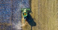 aerial view of a tractor on a farm field harvesting a crop