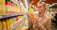woman shopping in a grocery store buying a bottle of juice