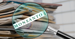 Magnifying glass with Monsanto logo underneath with stack of newspaper in backgroun