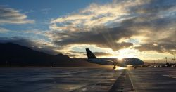 airplane at an airport waiting on a tarmac in front of a mountain range at sunset