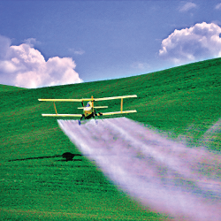 air plane spraying a crop field on a farm