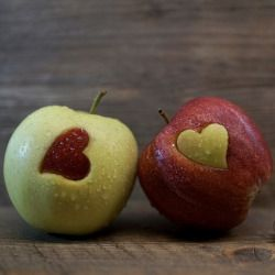 red and green apples with a cut out of a heart in each