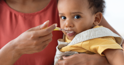 A baby eating from a spoon.