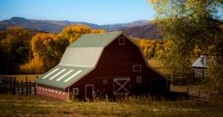 red barn building on a farm field in a mountain landscape at sunset