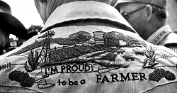 man wearing an embroidered shirt stating I'M PROUD TO BE A FARMER