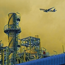 factory and an airplane against an orange sky