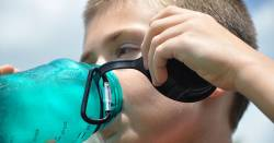 boy drinking from a plastic water bottle