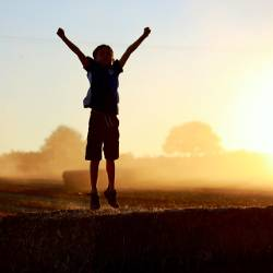 boy jumping for joy on a bale of hay in a farm field at sunset