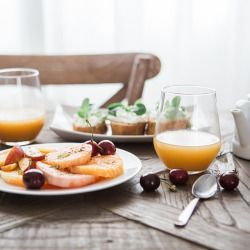 breakfast food on a table containing oranges and cherries with orange juice