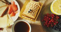 table set with breakfast foods including toast salmon blueberries and tea