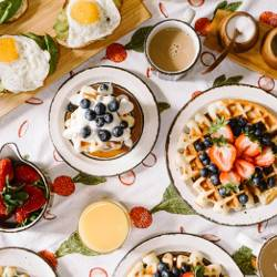 breakfast table set with food on plates like fried eggs and waffles with berries and fruit