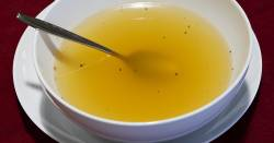 Clear yellow broth in a white bowl with a spoon