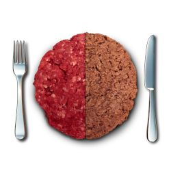 hamburger of half beef and half plant on a white table with a fork and knife