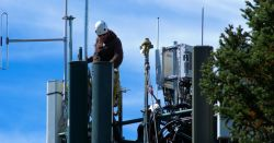worker performing maintenance on a cell phone tower