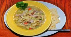 A bowl of chicken noodle soup with crackers