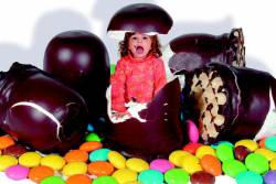 Child jumping out of life-sized chocolate junk food