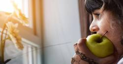 profile of a girl at a window taking a bite out of a green apple