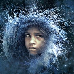 face of a young child surrounded by a spray of water