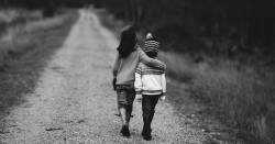 two children in sweaters walking down a dirt road