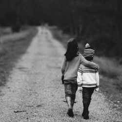 Two kids walking down road with one of their arms around the other's shoulders
