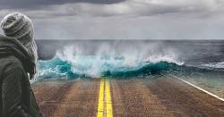 woman standing on the road as a tidal wave washes near