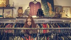 girl looking through clothes rack while shopping