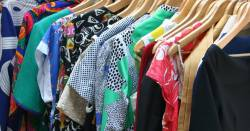 closet full of shirts dresses and other clothing on wooden hangers