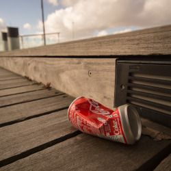 crushed red aluminum coca cola can on a board walk