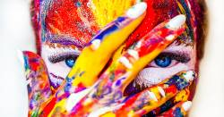woman with colorful paint for makeup covering her face with her hand