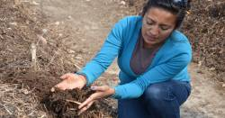 teacher displaying composted soil on a farm