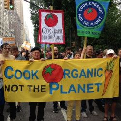 Ronnie Cummins at a protest march with several signs stating COOK ORGANIC NOT THE PLANET