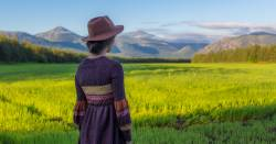 woman looking over a countryside farm field with mountains