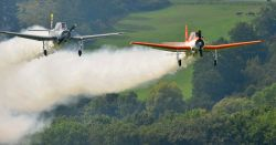 two crop duster airplanes spraying pesticides over a farm field