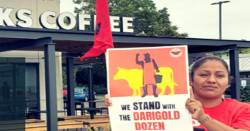 woman standing in protest with a sign outside of a Starbucks coffee shop