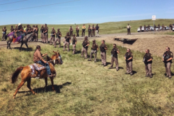 Lakota riders approach a police line that formed between a group of protesters and the entrance to the Dakota Access Pipeline construction site