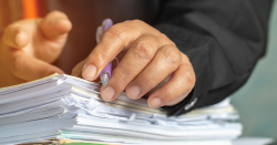 Person with hands and pen on a pile of documents.