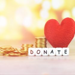 stacks of gold coins beside a red felt fabric heart and white and black blocks that spell DONATE