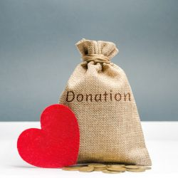 red felt heart beside a burlap bag and coins with the word DONATION