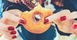 woman holding a sugared doughnut with a few bites taken out