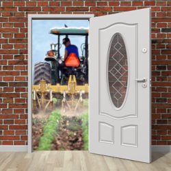 open door in a brick wall revealing a tractor on a farm crop field spraying herbicides