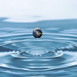 planet earth in a water droplet among ripples
