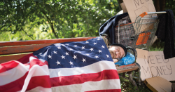 Man sleeping on a bench with an American flag as a blanket.