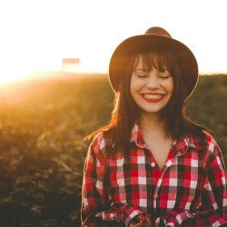 woman farmer in a crop field at sunset smiling