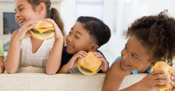 Kids eating burgers.