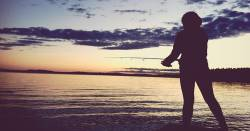 silhouette of a fishermen at the ocean shore