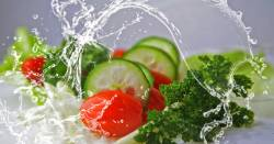 fresh produce in a vegetable salad splashed with water