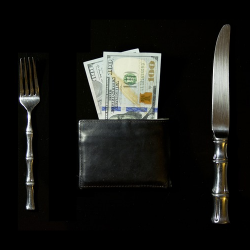 Money in wallet between a fork and a spoon
