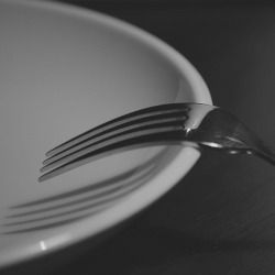 black and white image of a fork resting on a plate