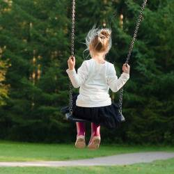 young girl swinging on a playground