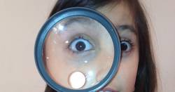 girl holding a magnifying glass to her eye